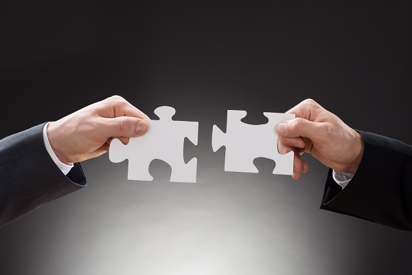 Close-up Of Two Businesspeople Connecting Jigsaw Puzzle Pieces