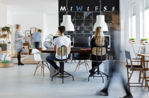 People in modern coworking space with blackboard calendar